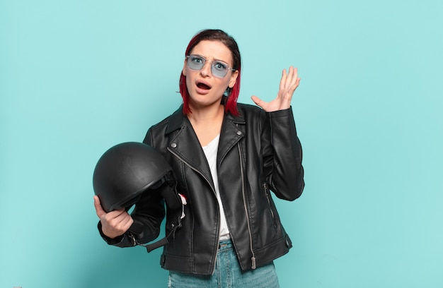 Young attractive red hair woman screaming with hands up in the air, feeling furious, frustrated, stressed and upset.