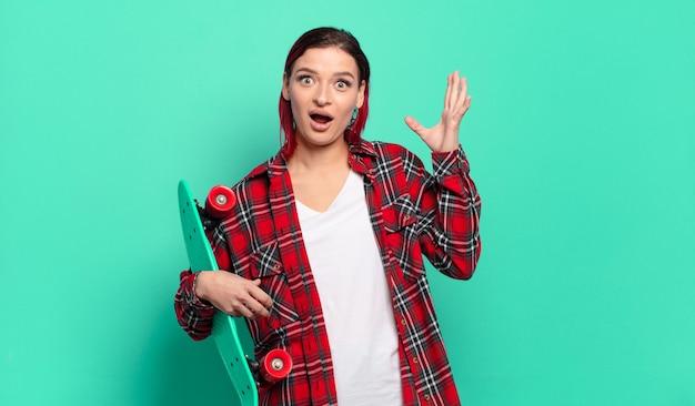 젊은 매력적인 빨간 머리 여자는 공중에서 손으로 비명을 지르고, 분노하고, 좌절하고, 스트레스를 받고, 화가 나서 스케이트 보드를 들고