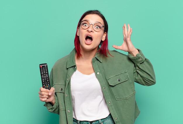 젊은 매력적인 빨간 머리 여자는 공중에서 손으로 비명을 지르고 분노하고 좌절감을 느끼고 스트레스를 받고 화가 나서 tv 리모컨을 들고 있습니다.