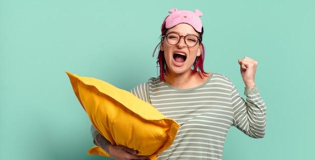 怒りの表情で、または成功を祝ってパジャマを着て握りこぶしで積極的に叫ぶ若い魅力的な赤い髪の女性。