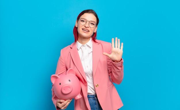 Молодая привлекательная женщина с рыжими волосами улыбается и выглядит дружелюбно, показывая номер пять или пятое с рукой вперед, считая. юмористическая бизнес-концепция.