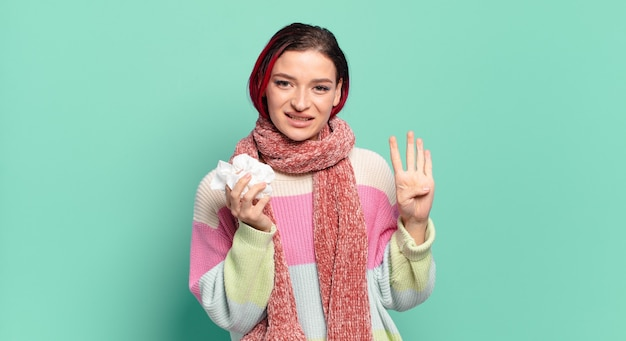 Молодая привлекательная женщина с рыжими волосами улыбается и выглядит дружелюбно, показывает номер четыре или четвертый с рукой вперед, считая концепцию гриппа