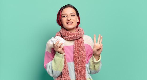 젊고 매력적인 빨간 머리 여성은 웃고 친근하게 보이며, 손을 앞으로 내미는 3번 또는 3번을 보여주며 독감 개념을 세고 있습니다.