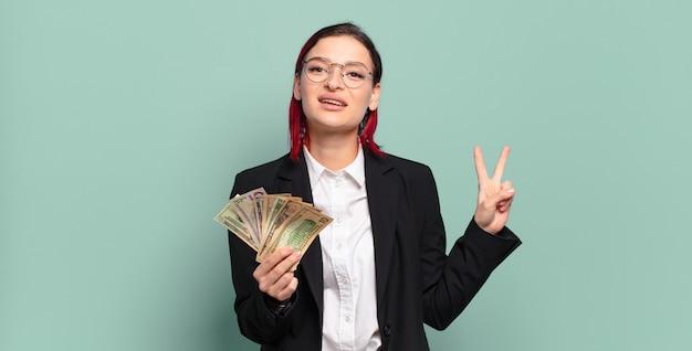 Молодая привлекательная женщина с красными волосами улыбается и выглядит дружелюбно, показывая номер два или секунду рукой вперед, считая. концепция денег