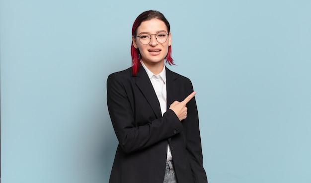 元気に笑って、幸せを感じて、横と上を指して、コピースペースでオブジェクトを示す若い魅力的な赤い髪の女性
