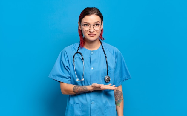 Young attractive red hair woman smiling cheerfully, feeling happy and showing a concept in copy space with palm of hand. hospital nurse concept