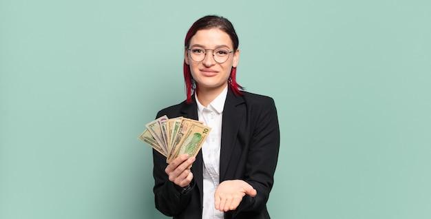 Молодая привлекательная женщина с рыжими волосами счастливо улыбается, дружелюбно, уверенно, позитивно смотрит, предлагая и показывая объект или концепцию