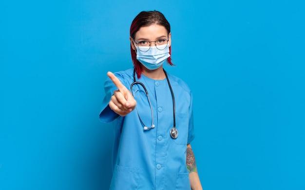 젊은 매력적인 빨간 머리 여자는 자랑스럽게 웃고 자신있게 넘버 원 포즈를 승리로 만들고 리더처럼 느끼고 있습니다. 병원 간호사 개념