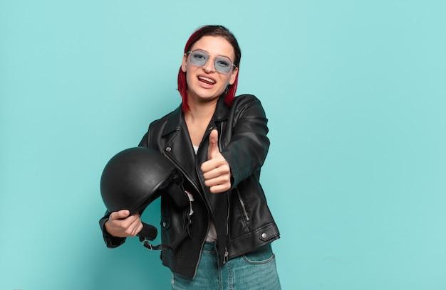 자랑스럽게 웃고 자신있게 넘버 원 포즈를 승리로 만드는 젊은 매력적인 빨간 머리 여자, 리더처럼 느낌