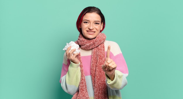誇らしげに自信を持って笑顔でナンバーワンのポーズを勝ち誇った若い魅力的な赤い髪の女性