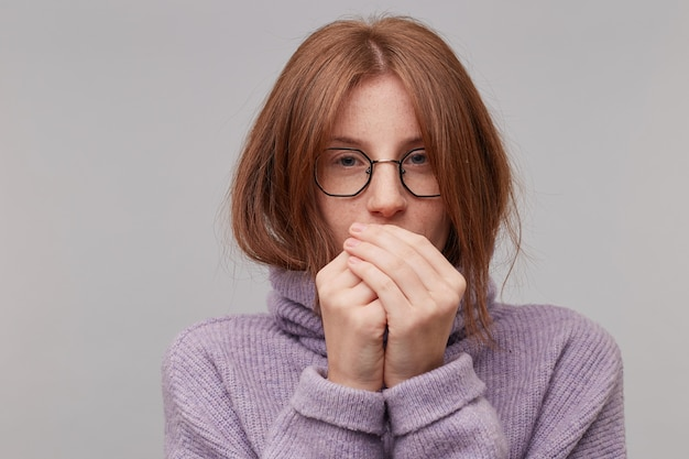 暖かい紫色のセーターに身を包んだ眼鏡の若い魅力的な赤毛の少女
