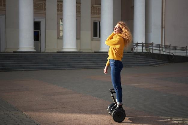 Молодая привлекательная рыжая кудрявая подтянутая женщина катается на ховерборде на улице