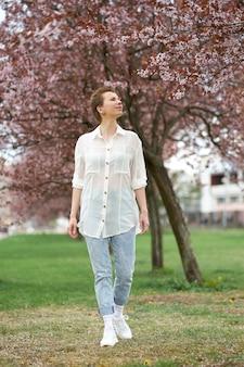 開花桜を背景にポーズをとる白いスタイリッシュなブラウスとジーンズを身に着けている若い魅力的な赤毛の女性。