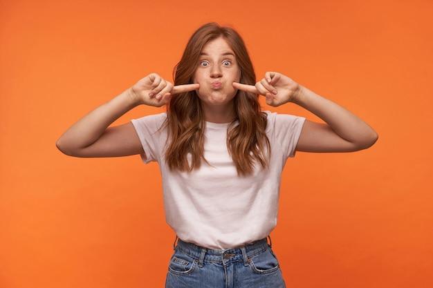 Молодая привлекательная рыжая женщина с кудрями корчит рожи, развлекается и поднимает указательные пальцы к щекам, в белой футболке и синих джинсах