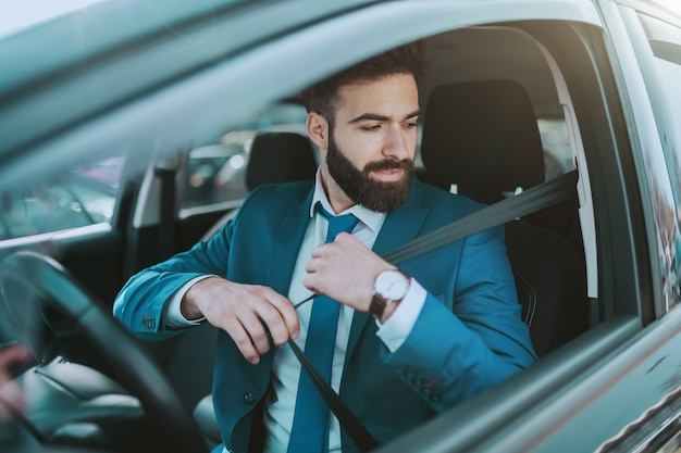 Young attractive responsible businessman fastening seat belt while sitting in his expensive car.