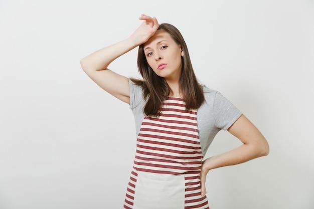 Молодая привлекательная грустная расстроенная утомленная домохозяйка брюнет кавказская в полосатом изолированном фартуке. женщина красивая домработница положила и коснулась ее руки к голове