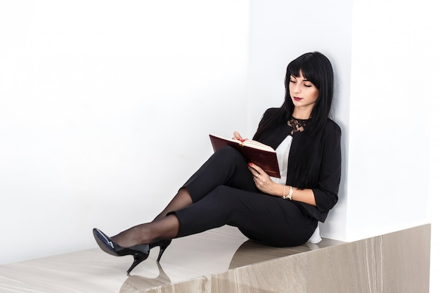 Young attractive serious brunette woman dressed in a black business suit sitting on a floor in a office, writing in a notebook.