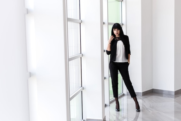 Young attractive serious brunette woman dressed in a black business suit standing near the window in office, looking at camera.