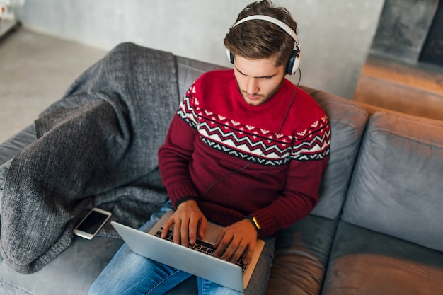 Young attractive serious concentrated man sitting on sofa at home in winter, wearing red knitted sweater, working on laptop, freelancer, busy, listening to headphones, typing, studying online