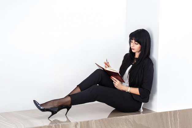 Young attractive serious woman  sitting on a floor in a office, reading in a notebook.
