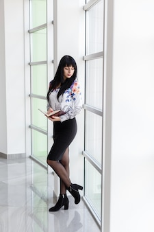 Young attractive serious woman standing near the window in a office, holding a  notebook, looking out to window.