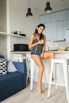 Молодая привлекательная сексуальная женщина завтракает на стильной современной кухне утром, ест яблоко, улыбается, счастливый, позитивный, здоровый образ жизни, слушает музыку в наушниках, смеется, веселится