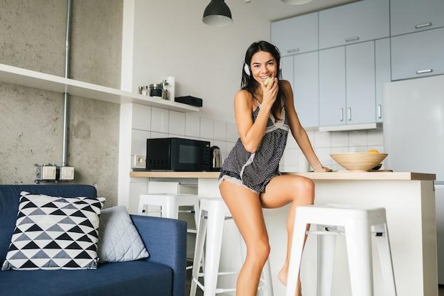 Giovane donna sexy attraente fare colazione in cucina moderna ed elegante mattina, mangiare mela, sorridente, felice, positivo, stile di vita sano, ascoltare musica in cuffia, ridere, divertirsi