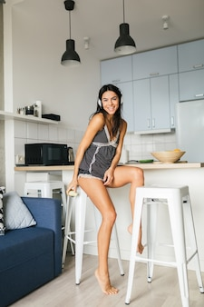 Young attractive sexy woman having breakfast in stylish modern kitchen in morning, eating apple, smiling, happy, positive, healthy lifestyle, listening to music on headphones, laughing, having fun