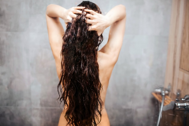 Young attractive sexy woman in shower. dark-haired caucasian model with well-built slim body stand and hold hair between hands. beautiful shape.