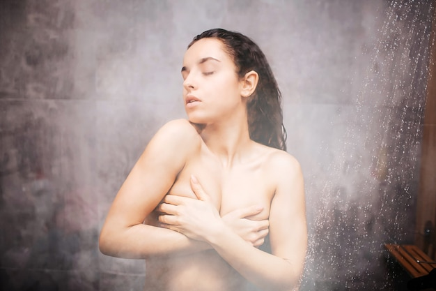 Young attractive sexy woman in shower. enjoyment during washing herself. covering breast with hands. eyes closed. water vapor on glass wall. semi blurred picture.