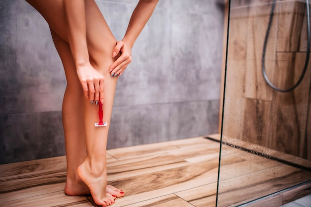 Young attractive sexy woman in shower. naked body. she shave legs using sharp razor. posing. well-buil and sporty. dry shaving. cut view.