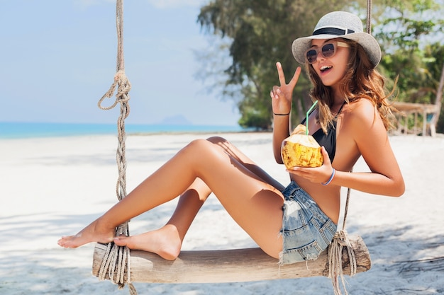 Young attractive sexy woman on vacation sitting on swing by sea, tropical beach, drinking cocktail in coconut, skinny legs, traveling in thailand, smiling, happy, positive emotion, summer style