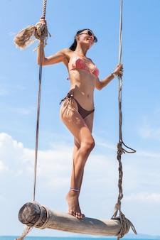 Giovane donna sexy attraente in vacanza che si siede sull'altalena dal mare, spiaggia tropicale, gambe magre, viaggiando in thailandia, sorridente, felice, emozione positiva, stile estivo