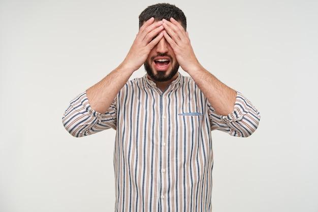 カジュアルな服装で白い壁の上にポーズをとっている間、彼の目に上げられた手のひらを維持しているひげを持つ若い魅力的な短い髪のブルネットの男