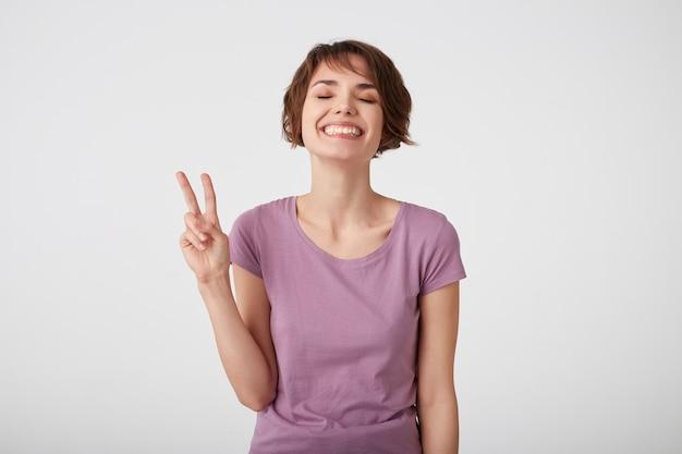 若い魅力的な短い髪の幸せな女の子、手でピースサインを作り、幸せを表現し、屋内でカジュアルなシャツのポーズを着て、白い壁の上に立って、広く笑顔。ポジティブな感情の概念。