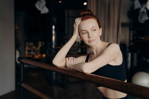 Young attractive slender woman ballerina with red hair leaning on ballet barre in meditative facial expression during stretching workout in fitness studio, resting and thinking about something
