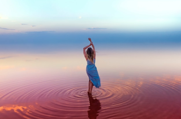 Young attractive slender woman in a blue dress in the pink water of a salt lake, on a surface of blue sky