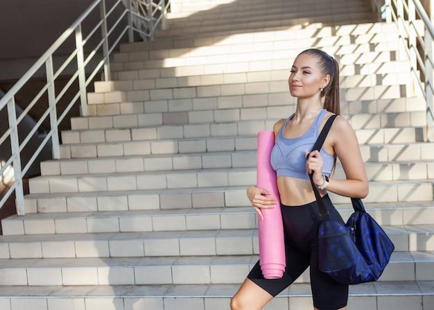 Молодая привлекательная стройная женщина в спортивной одежде готовится к тренировке с тренировочной сумкой и ковриком в руке
