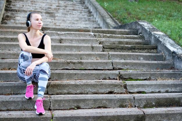 Молодая привлекательная стройная спортивная девушка сидит на лестнице и слушает музыку.