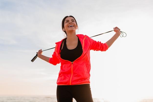 Молодая привлекательная стройная женщина делает спортивные упражнения в утреннем восходе солнца на морском пляже в спортивной одежде, здоровом образе жизни, слушает музыку в наушниках, в розовой куртке-ветровке, держит скакалку