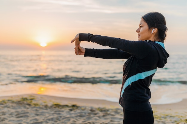 Young attractive slim woman doing sport exercises on morning sunrise beach in sports wear, healthy lifestyle, listening to music on earphones, making stretching for arms