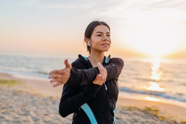 Giovane donna attraente sottile facendo esercizi sportivi sulla spiaggia di alba di mattina in abbigliamento sportivo, stile di vita sano, ascoltando musica con gli auricolari, facendo stretching per le mani