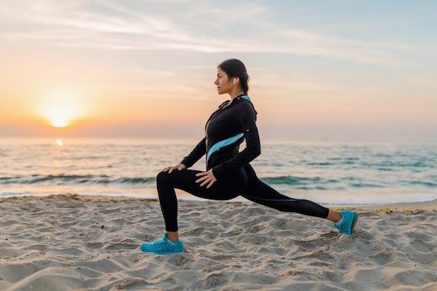 Giovane donna attraente sottile facendo esercizi sportivi sulla spiaggia di alba di mattina in abbigliamento sportivo, stile di vita sano, ascoltando musica con gli auricolari, facendo stretching per le gambe