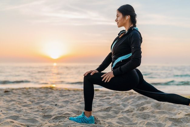 Young attractive slim woman doing sport exercises on morning sunrise beach in sports wear, healthy lifestyle, listening to music on earphones, making stretching for legs