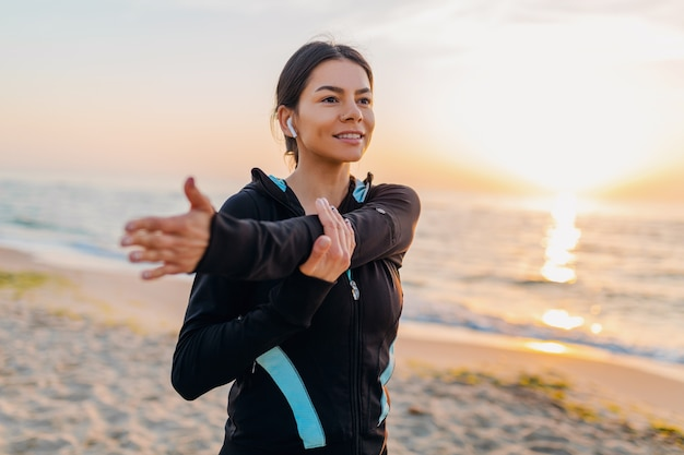 Young attractive slim woman doing sport exercises on morning sunrise beach in sports wear, healthy lifestyle, listening to music on earphones, making stretching