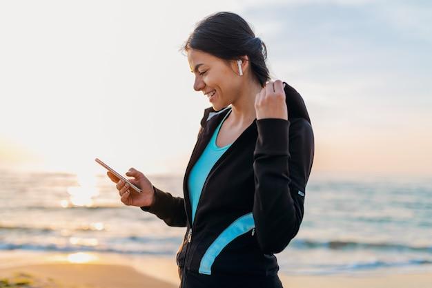 Giovane donna attraente sottile facendo esercizi sportivi sulla spiaggia di alba di mattina in abbigliamento sportivo, stile di vita sano, ascoltando musica su auricolari wireless che tengono smartphone, sorridendo felice divertendosi