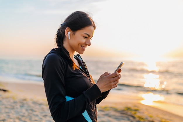 Young attractive slim woman doing sport exercises on morning sunrise beach in sports wear, healthy lifestyle, listening to music on wireless earphones holding smartphone, smiling happy