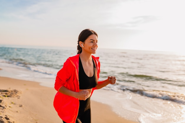 Giovane donna attraente sottile facendo esercizi sportivi all'alba mattutina a fare jogging sulla spiaggia del mare in abbigliamento sportivo, stile di vita sano, ascolto di musica sugli auricolari, indossa una giacca a vento rosa