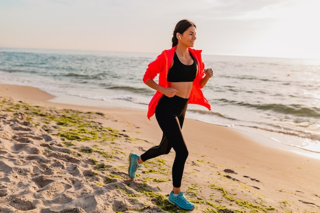 Young attractive slim woman doing sport exercises in morning sunrise jogging on sea beach in sports wear, healthy lifestyle, listening to music on earphones, wearing pink windbreaker jacket
