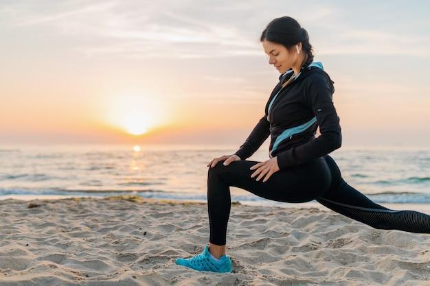 Молодая привлекательная стройная женщина делает спортивные упражнения на утреннем пляже восхода солнца в спортивной одежде, здоровом образе жизни, слушает музыку в наушниках, делает растяжку для ног